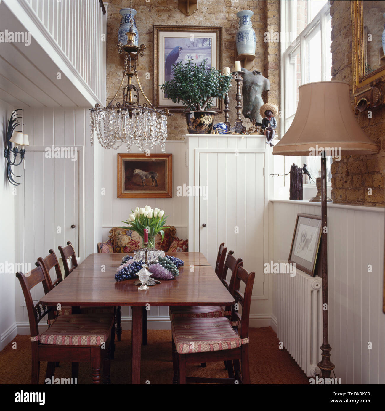 Chandelier Above Antique Table And Chairs In Small White Paneled Double Height Dining Room