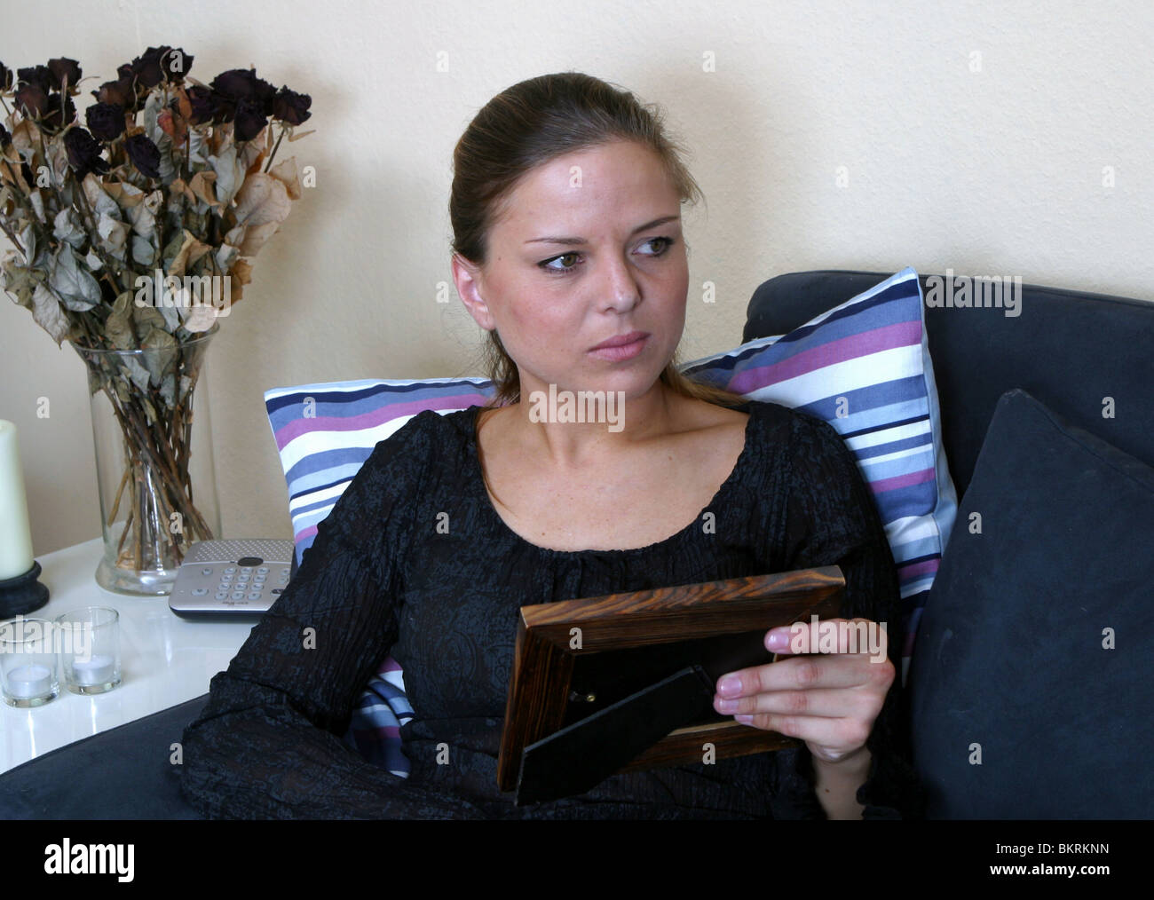 Front view head and shoulders from a woman holding photo frame in hand sitting on couch indoors and looking worried - Stock Image