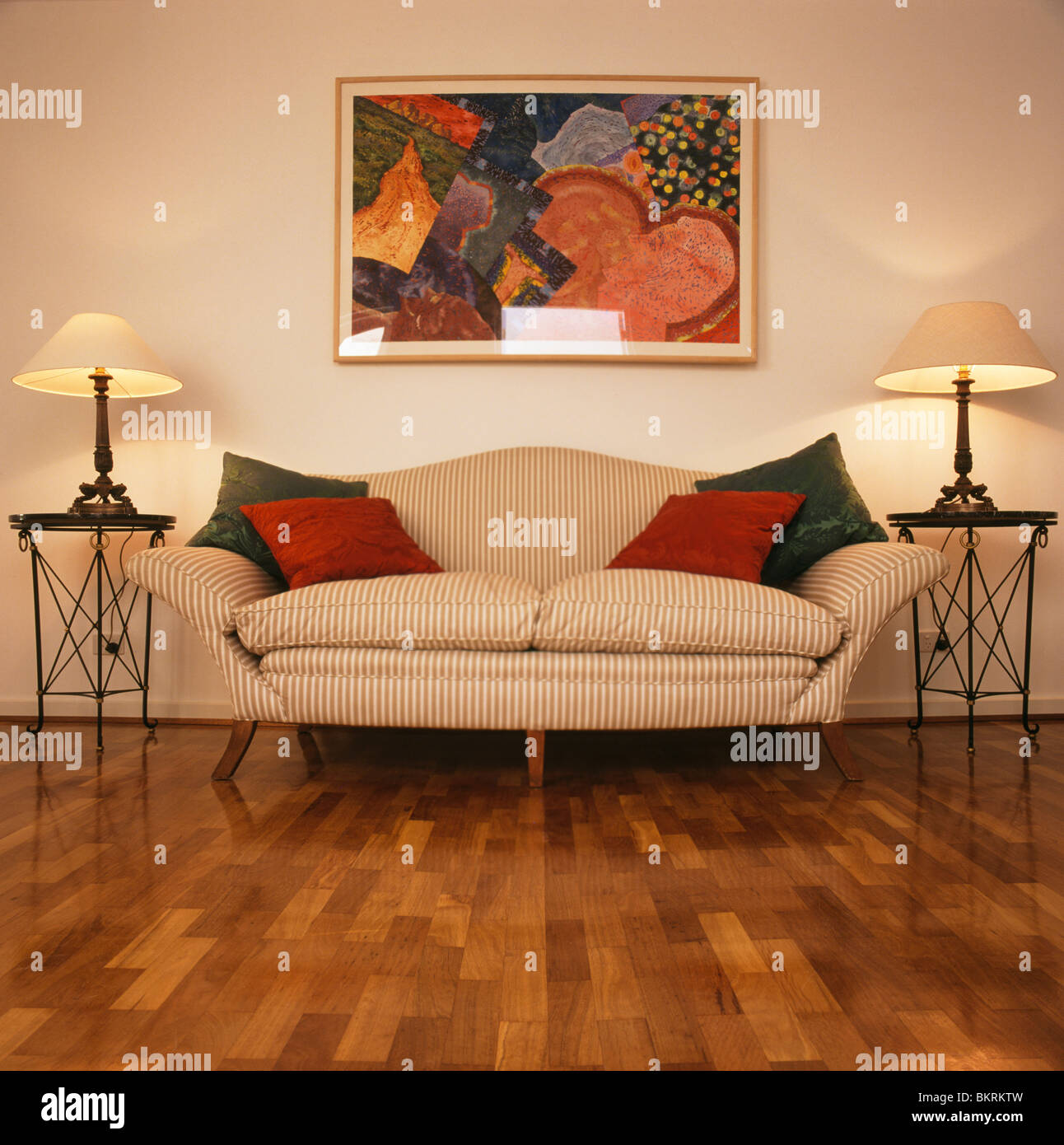 Colorful picture on wall above on striped cream sofa with modern ...
