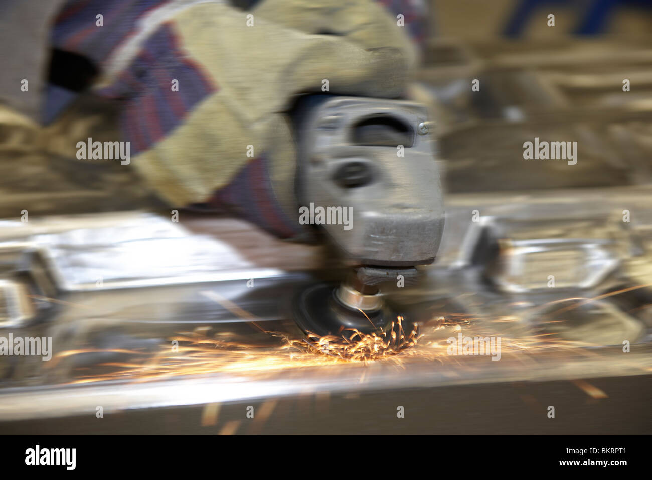 man using a angle grinder on metal surface with movement - Stock Image