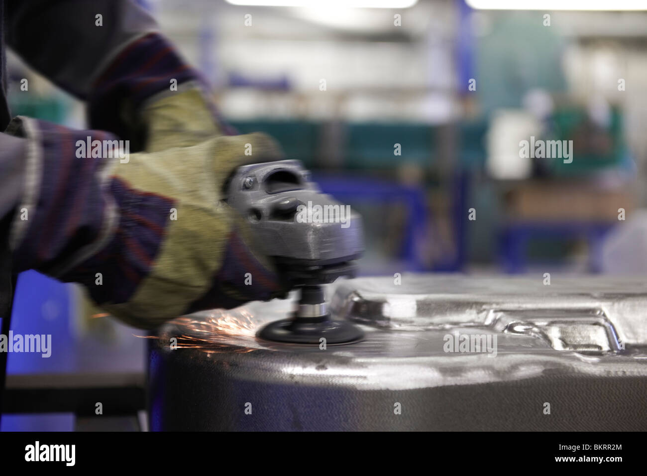 man using a angle grinder on metal surface with sparks - Stock Image