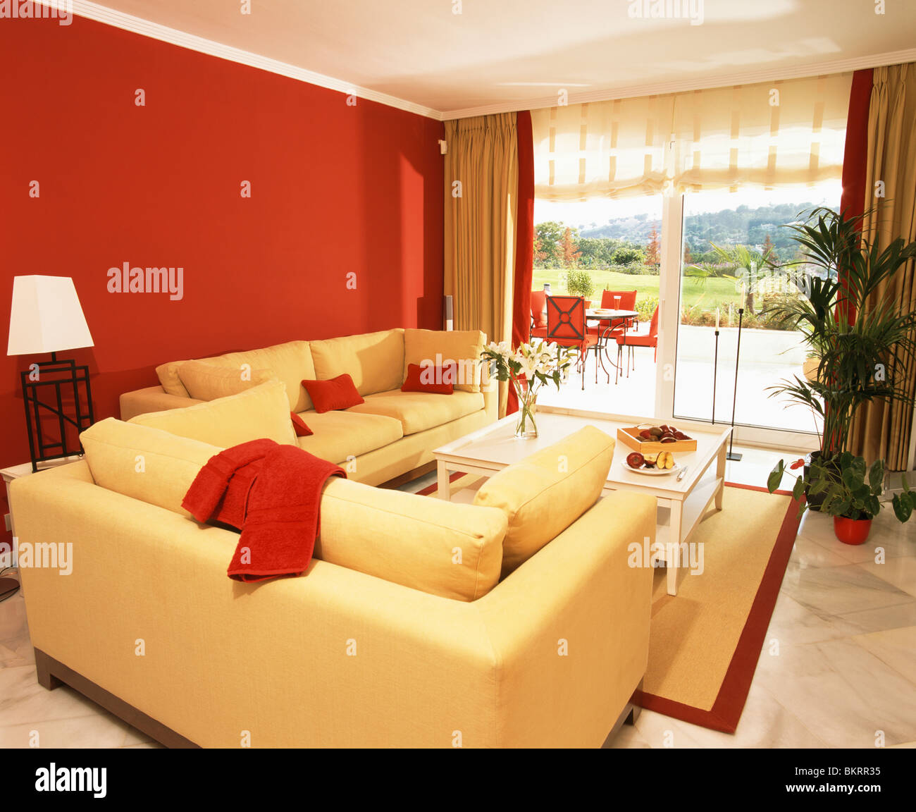 Bright yellow sofas and red wall in modern living room with French ...