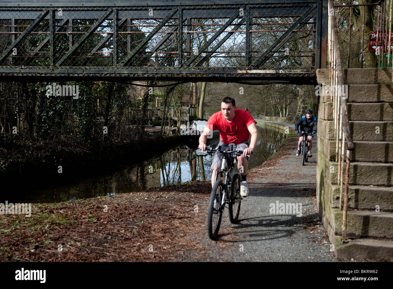 Man on a bike riding along the canal towpath Derbyshire England UK - Stock Image