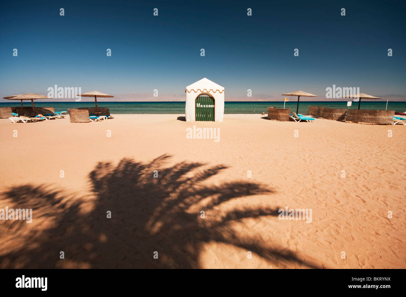 An exotic and beautiful beach on the Egyptian coastline with a shadow of a palm tree and the customary umbrellas - Stock Image