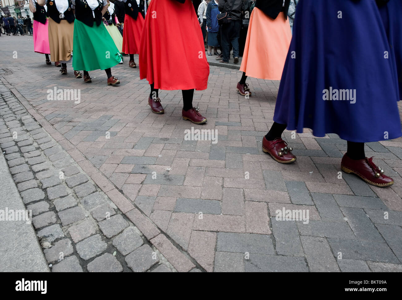 A Ladies Morris team wearing colourful skirts dancings at the Sweeps Festival - Stock Image