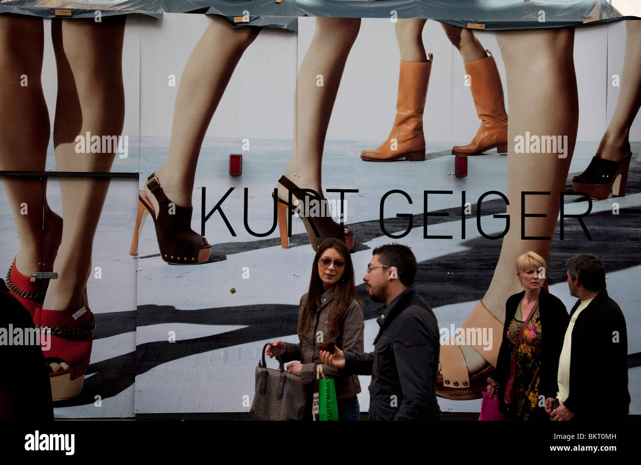 People pass a large fashion poster for Kurt Geiger. Covent Garden in the West End of London. - Stock Image