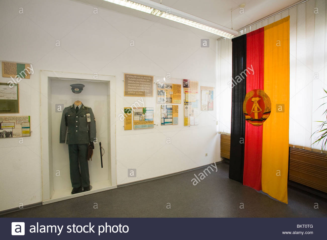 lag of the DDR and uniform of the Stasi,the secret center of the Stasi in the days of the GDR,the Stasi Museum,Berlin,Germany - Stock Image