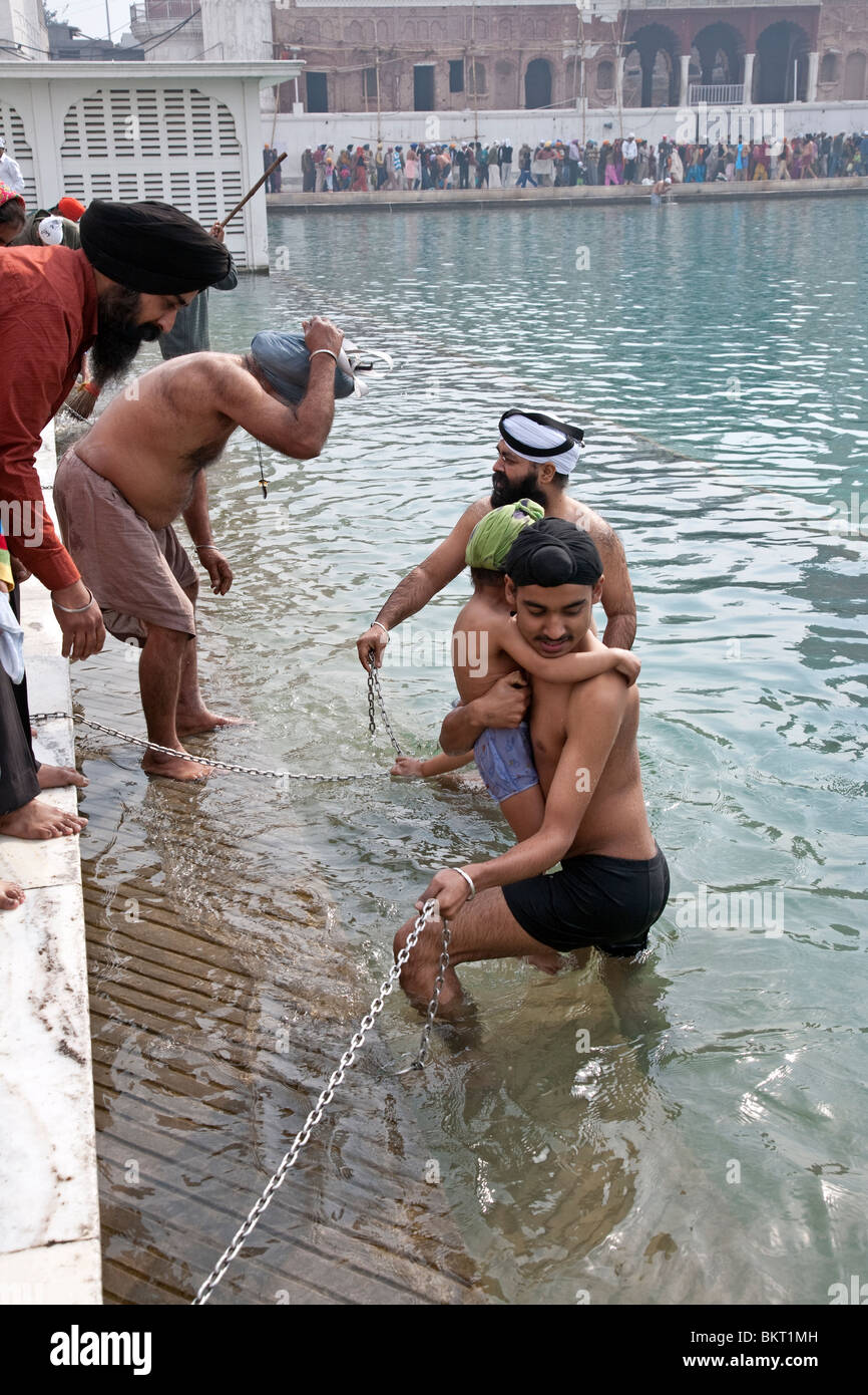 Sikhs devotees taking the ritual bath in the sacred pool. The Golden Temple. Amritsar. Punjab. India Stock Photo
