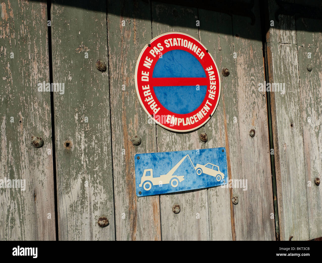 No Parking sign and Tow-away sign on old wood door. - Stock Image