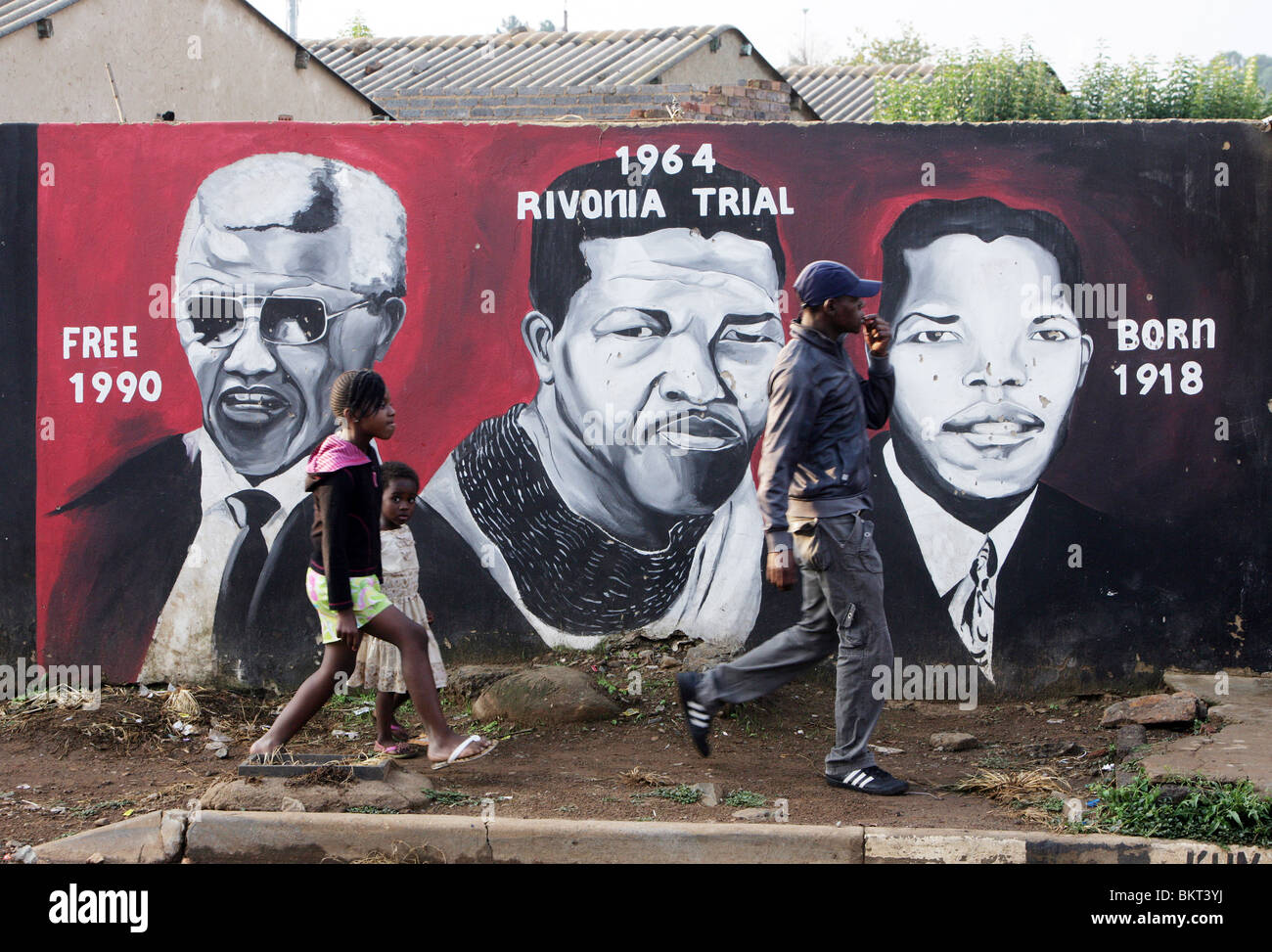 Children passing a Nelson Mandela wall mural in the Township Soweto, Johannesburg, South Africa - Stock Image