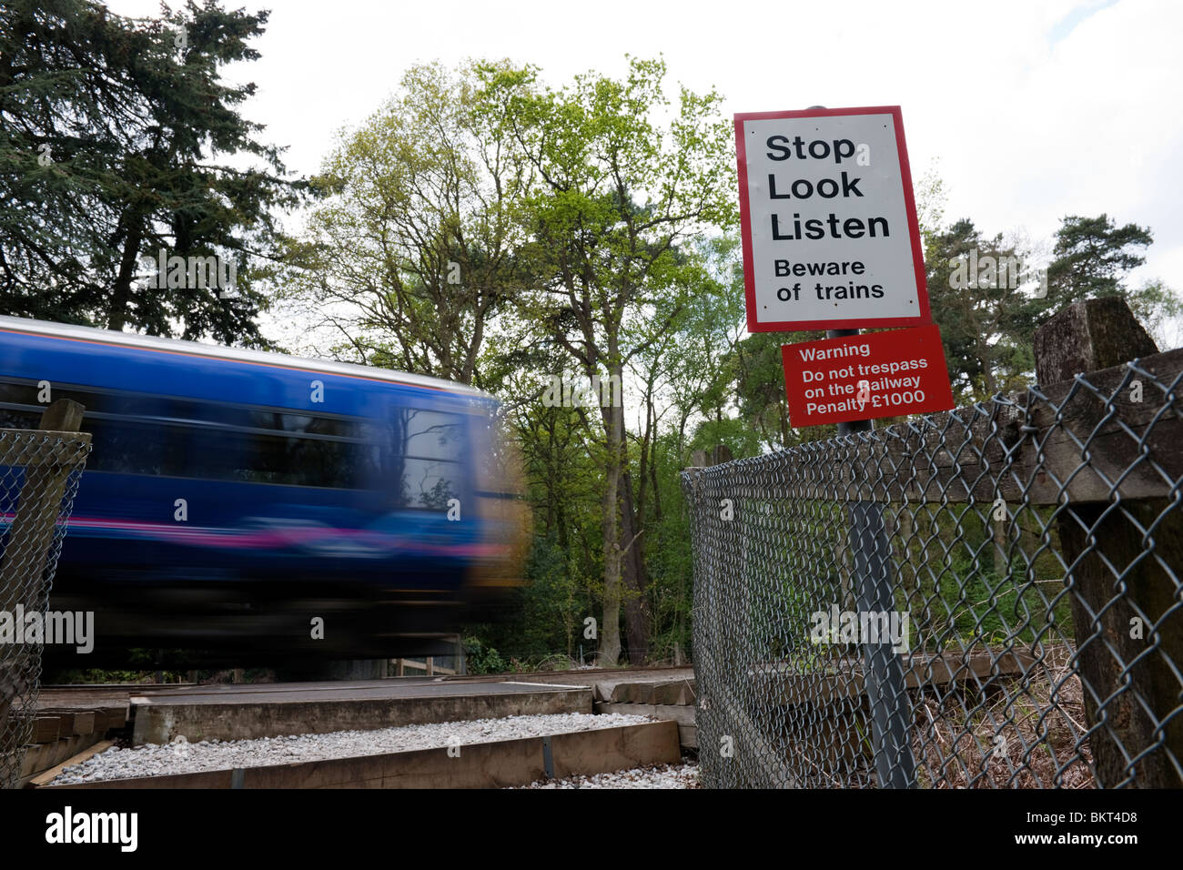 Footpath level crossing with Stop Look and Listen board and fast train passing - 1 - Stock Image