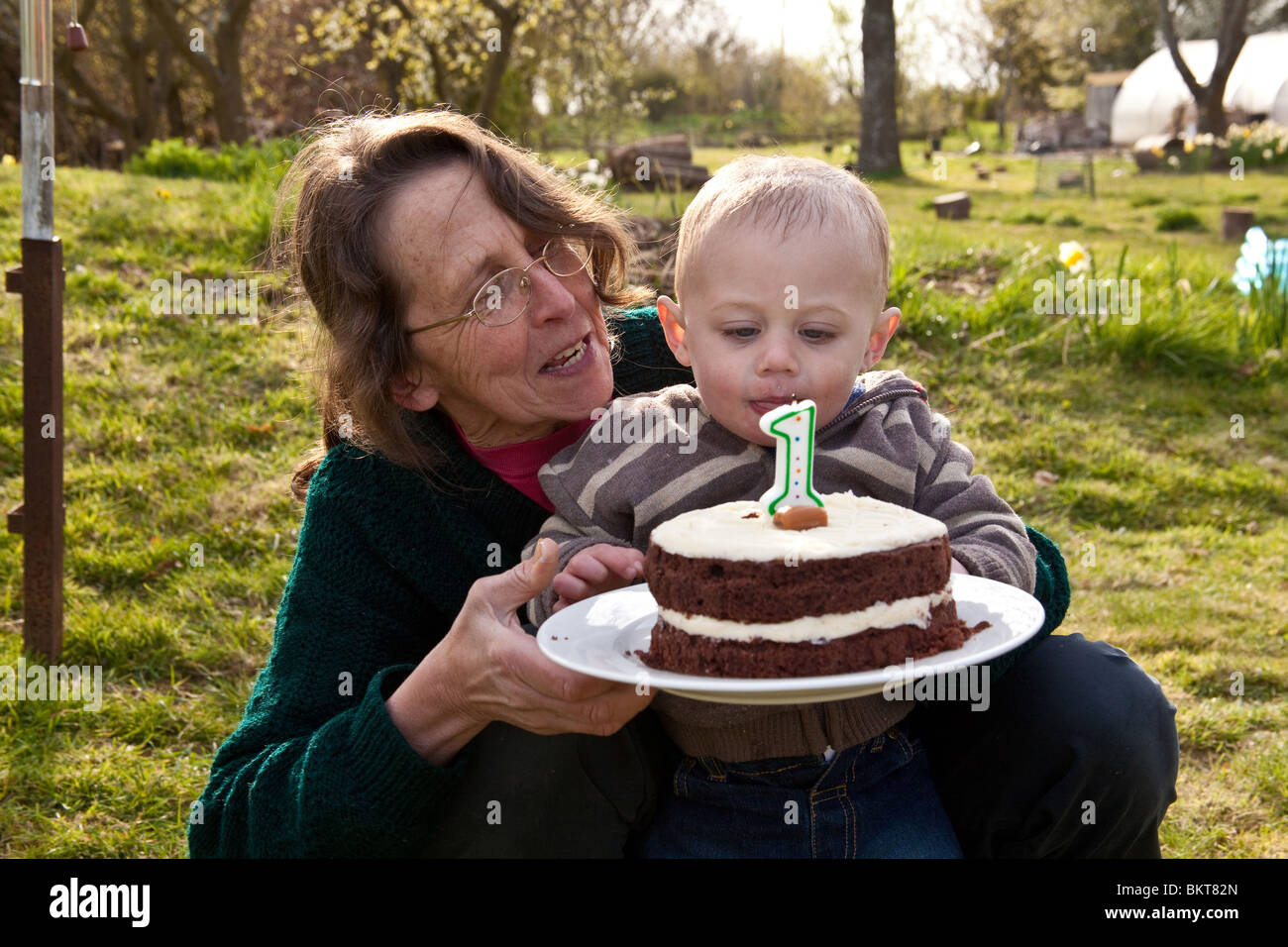 One Year Old Baby Boy Outside With His Birthday Cake And Grandmother