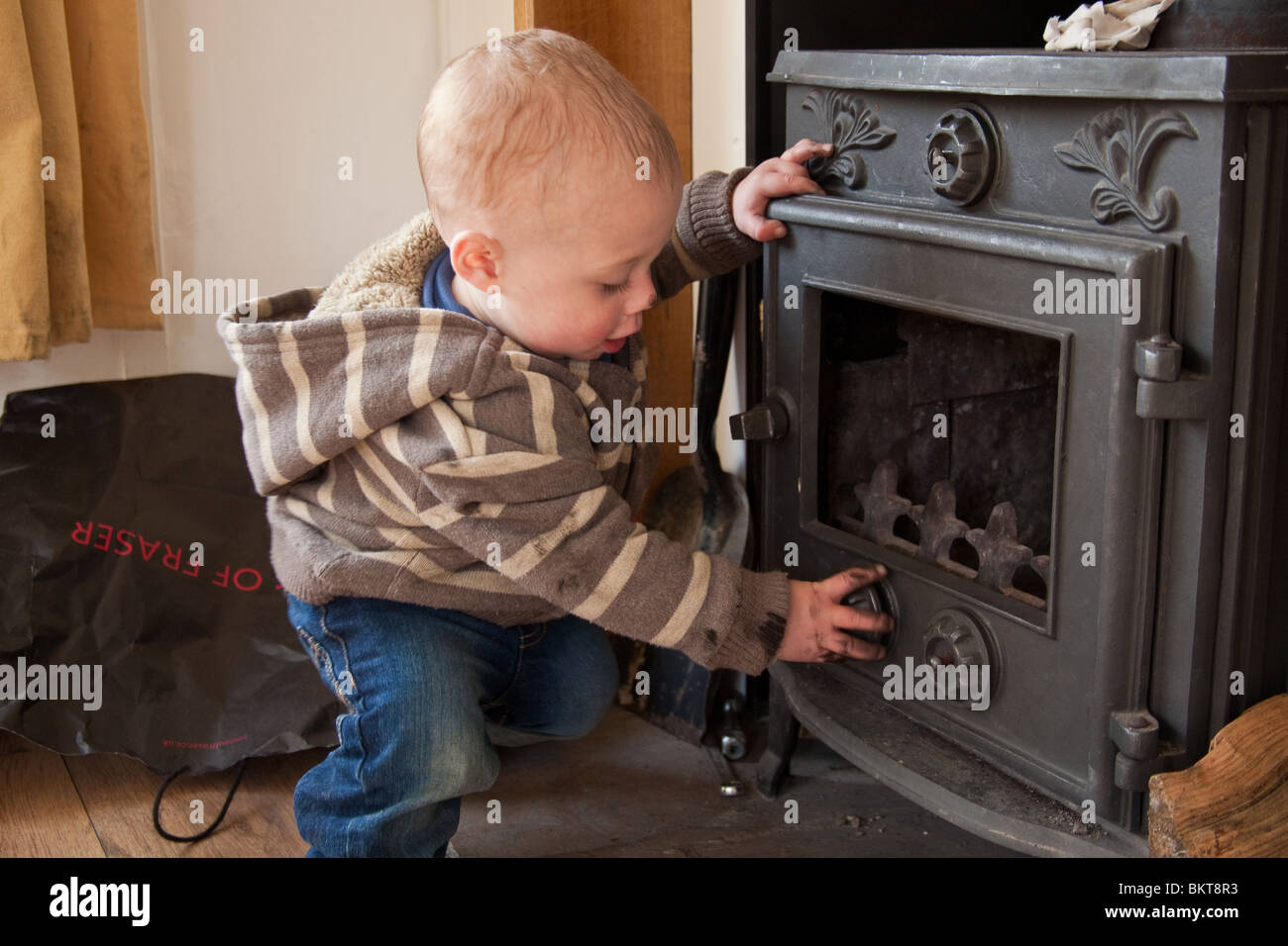 Baby boy ( 1 year old ) playing with a wood burning stove. Hampshire, England. - Stock Image