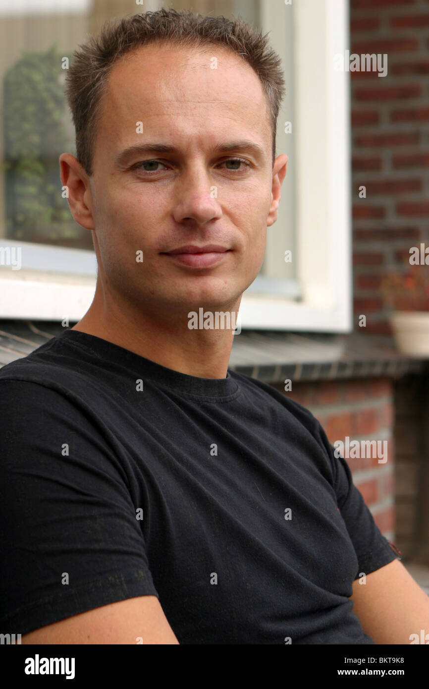 Serious face of an adult man : portrait 30s sit on front porch bench - Stock Image