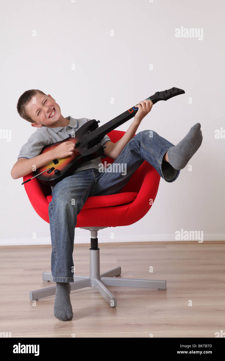 Young boy playing on guitar video game - Stock Image