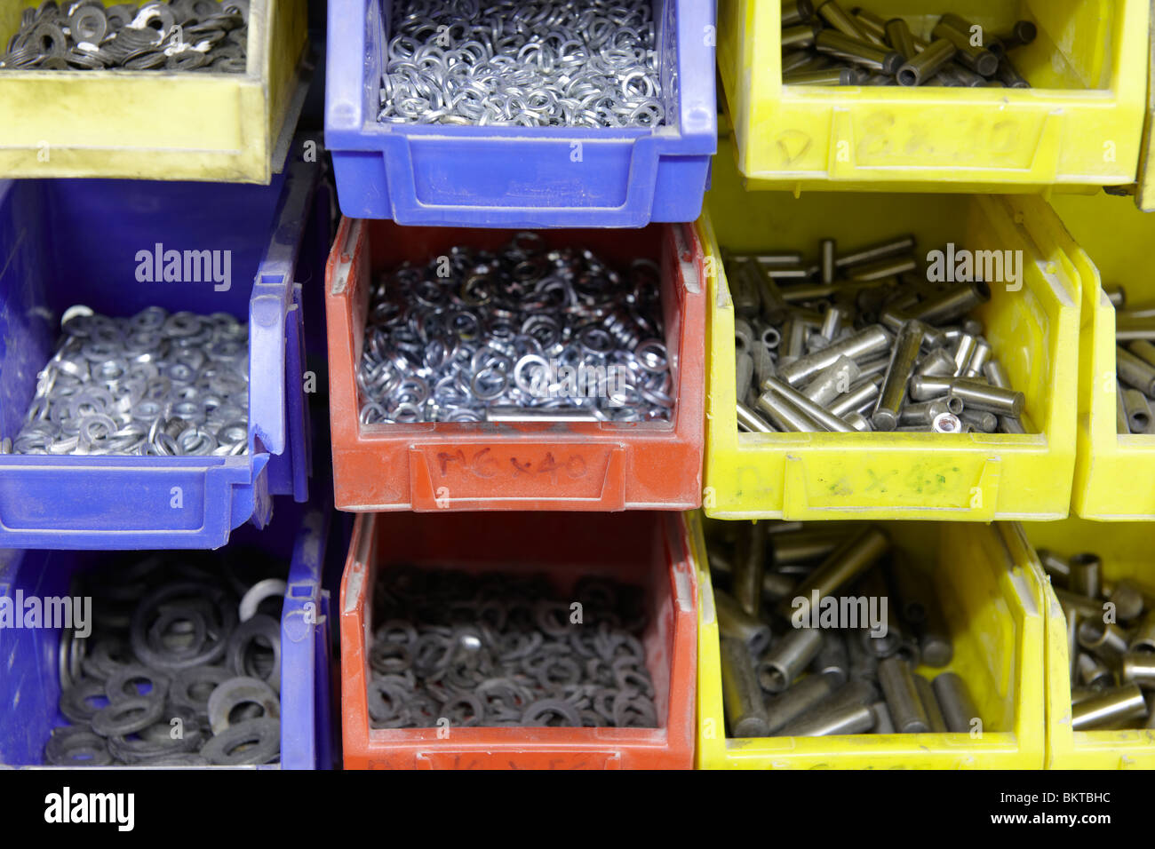 metal washers in different coloured storage trays on factory floor - Stock Image