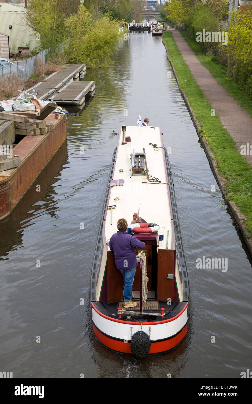A woman at the tiller of a canal narrow boat as it passes along the