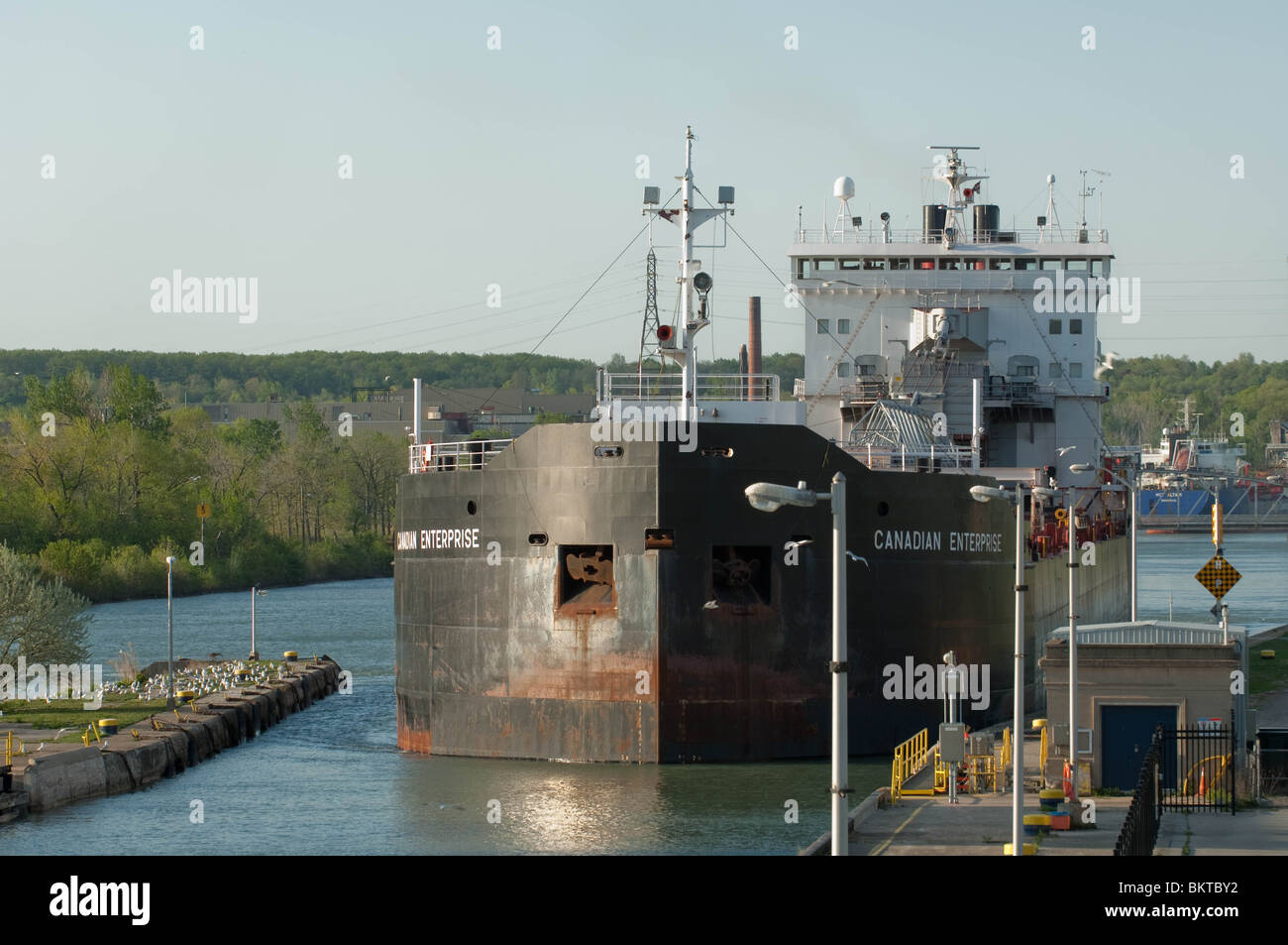 Great Lakes bulk cargo Carrier maneouvers to enter Lock 3 of the Welland Canal. - Stock Image