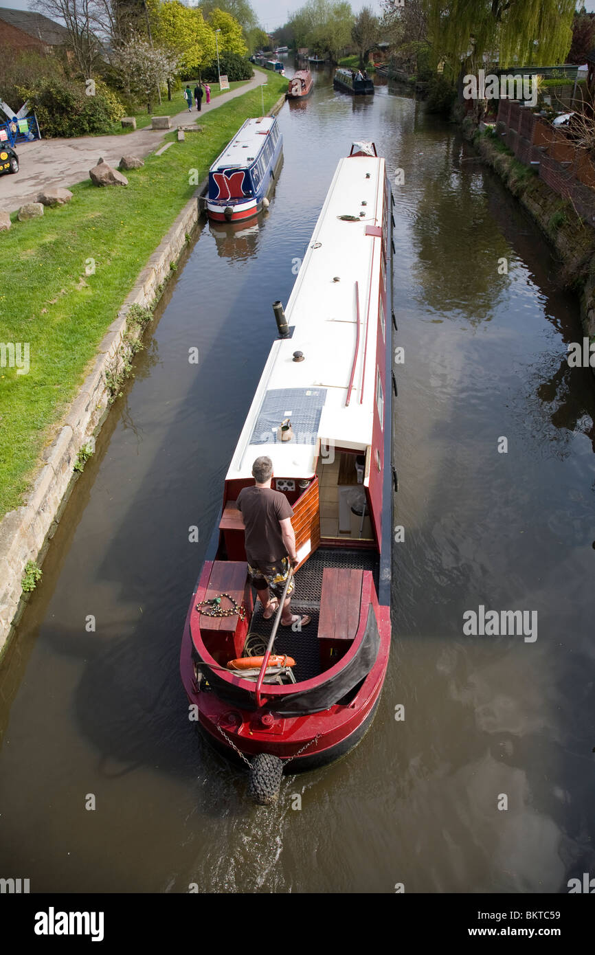 A man at the tiller of a canal narrow boat on the Grand Union Canal, Loughborough, Leicestershire. - Stock Image