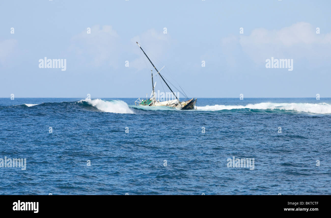 Wreck of a yacht on the rocks off the coast of Santa Cruz in the Galapagos Islands - Stock Image