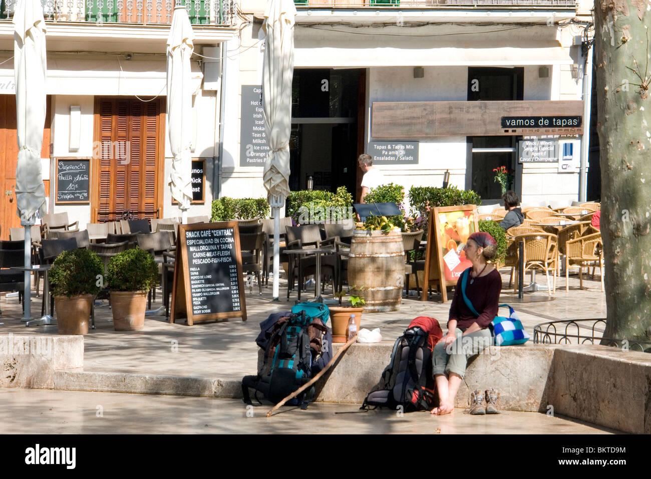 A Lady hiker resting at the main square of Soller (Majorca - Spain). Randonneuse se reposant sur la place principale - Stock Image