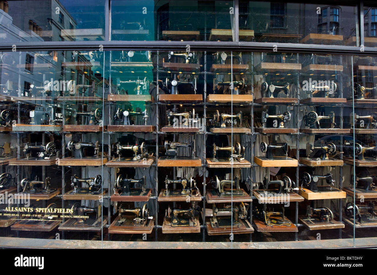 A shop window display full of old fashioned Singer sewing machines, a fashion  clothes shop in Brighton, Sussex - Stock Image