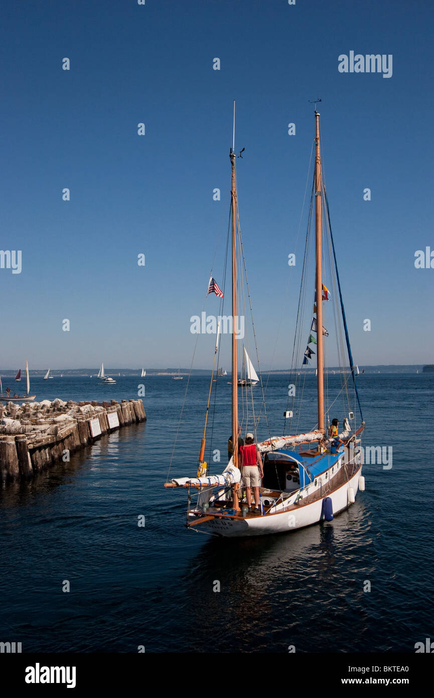 Sailboat leaving port on sunny summer day - Stock Image