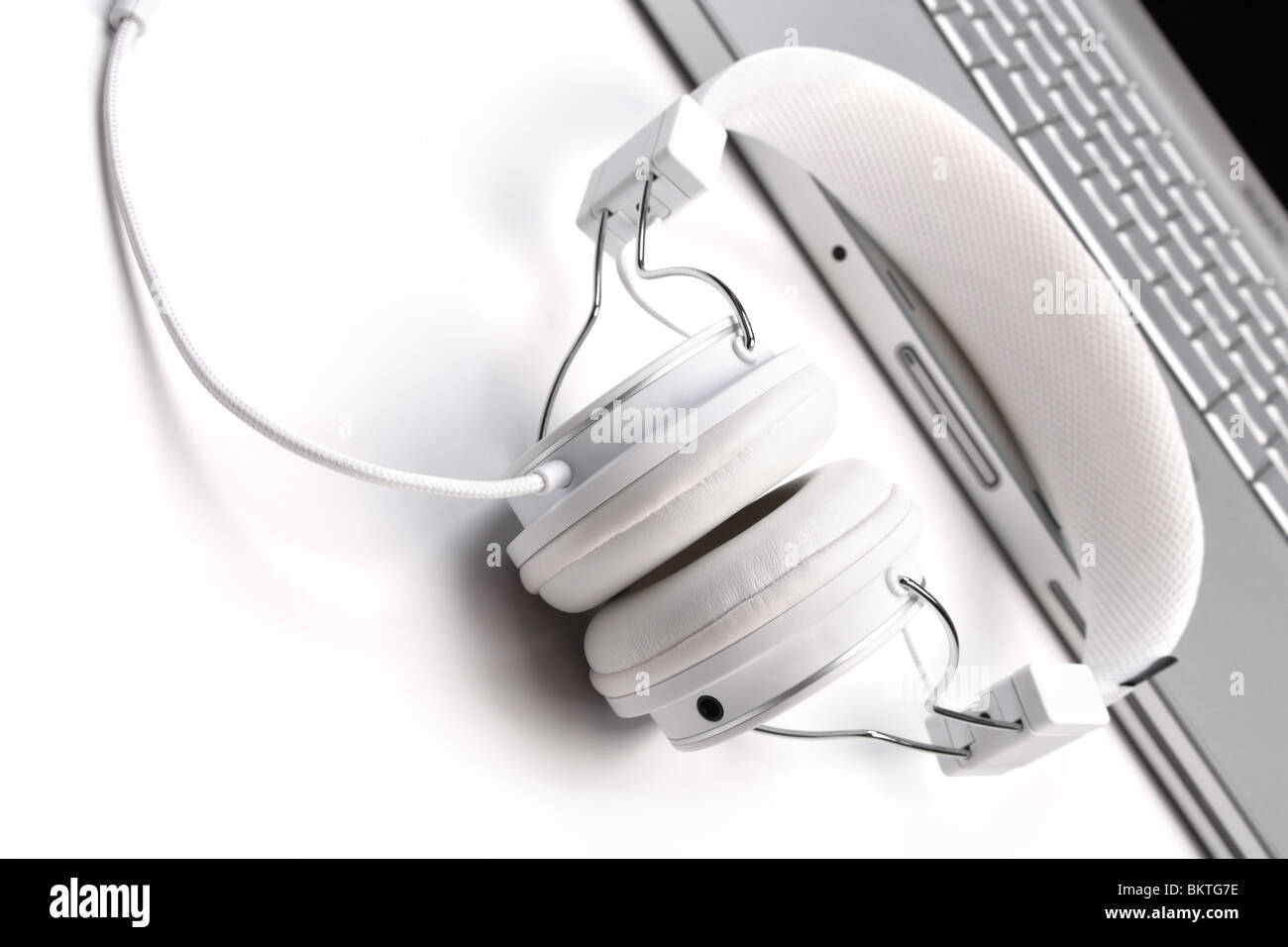White elegance headphones and laptop on white background, tilt view. - Stock Image