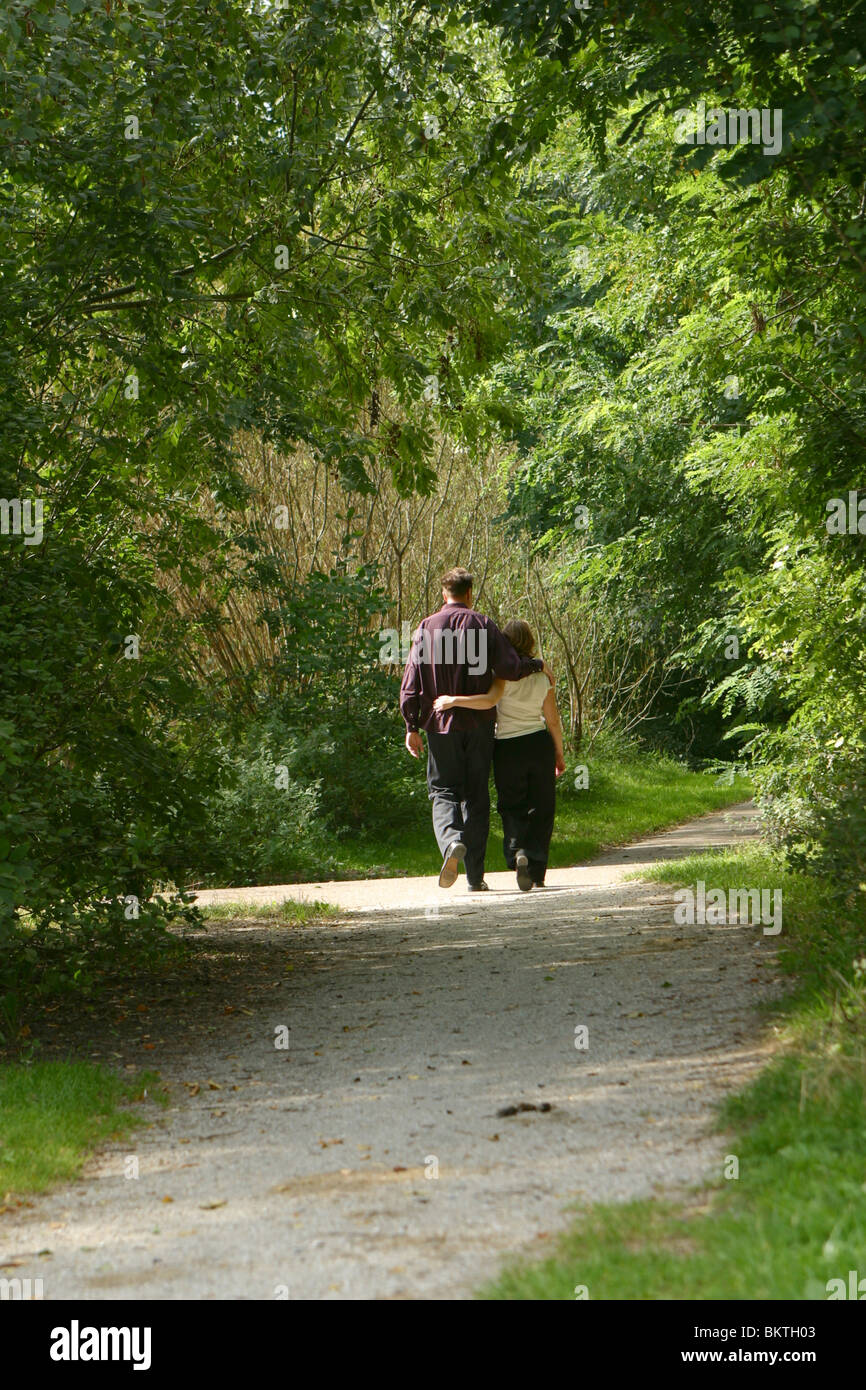 Adult couple and romantic walk they enjoy nature while walking in the forest in summer third trimester pregnancy