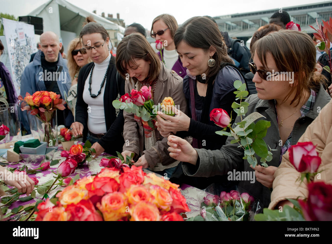 Crowd of People Taking Roses at Florist Stall at Celebration of World 'Fair Trade' Day, La Villette Park, - Stock Image