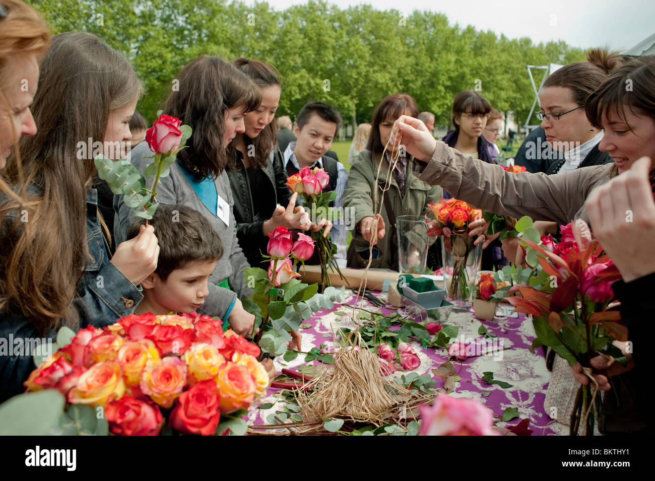 Crowd of People, Taking Roses at Florist Stall at Celebration of World 'Fair Trade' Day, La Villette Park, - Stock Image