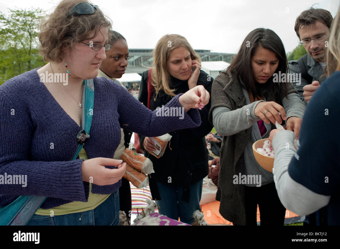 Celebration of World 'Fair Trade' Day, with People Taking Free Trade Cotton Samples on Lawn of La Villette - Stock Image