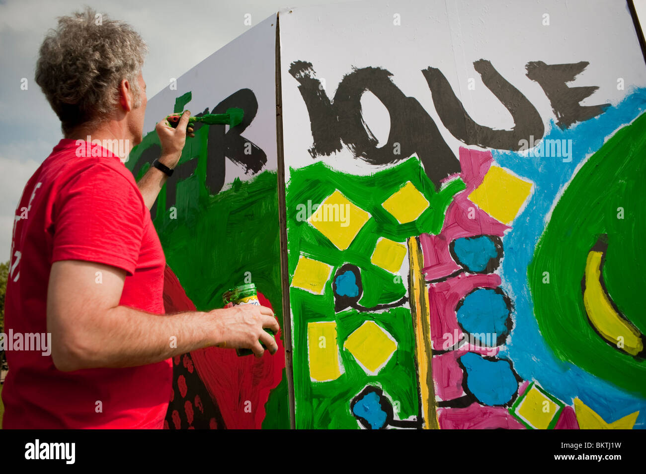 Celebration of World 'Fair Trade' Day, with Man Painting Wall, on Lawn of La Villette Park, to Encourage - Stock Image
