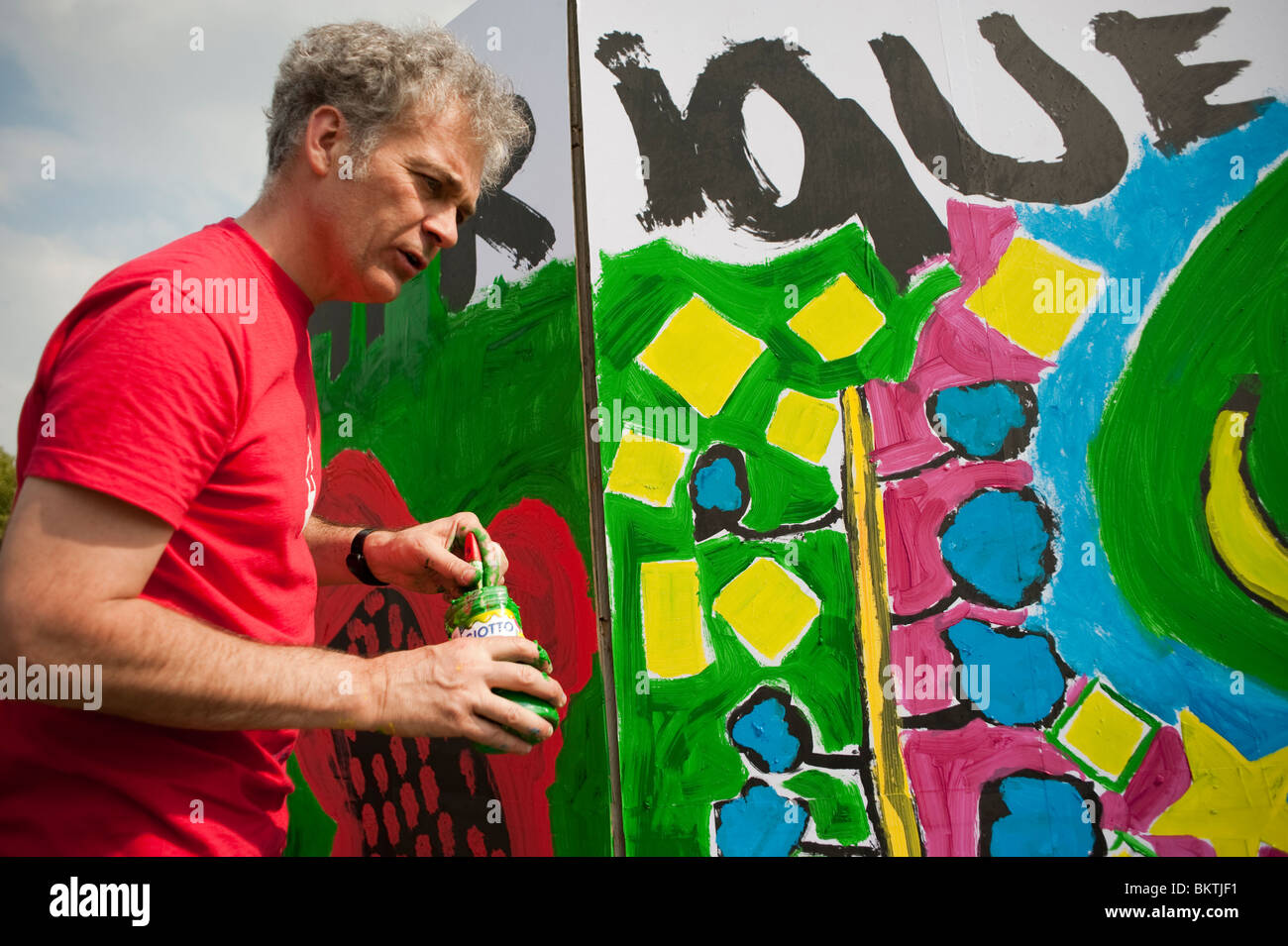 Celebration of World 'Fair Trade' Day, with Man Painting Wall Mural in 'La Villette' Park, - Stock Image