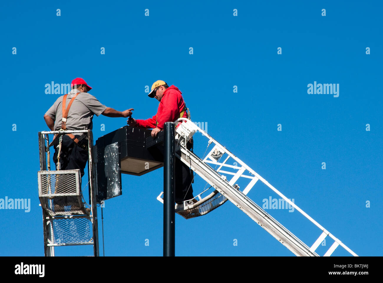 maintenance workers work as a team to repair a lighting fixture - Stock Image