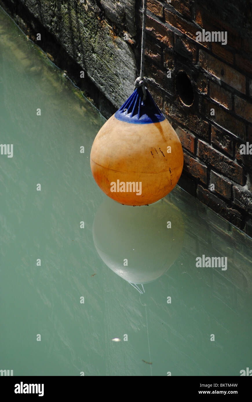 Orange buoy in a canal, Venice, Italy - Stock Image