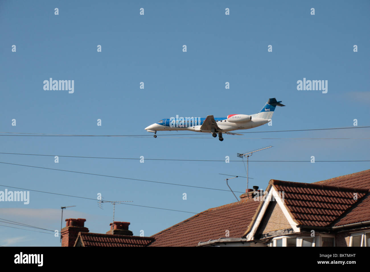 A BMI Regional Embraer EMB-135ER (ERJ-135ER) landing at Heathrow Airport, London, UK. View fm Myrtle Avenue, Hounslow. - Stock Image