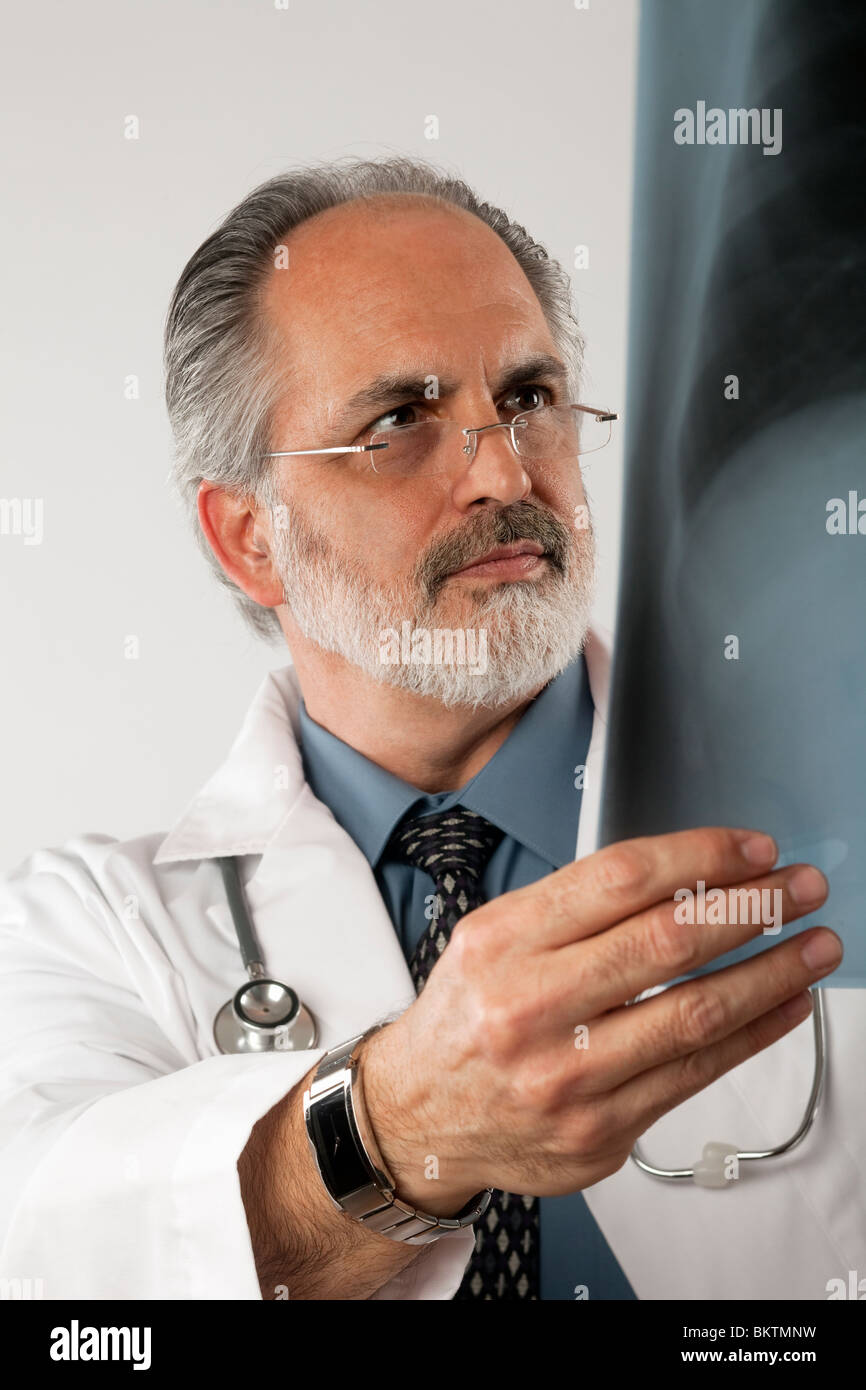 Portrait of a doctor wearing eyeglasses and a white lab coat and looking intently at an x-ray. Vertical shot. Isolated - Stock Image