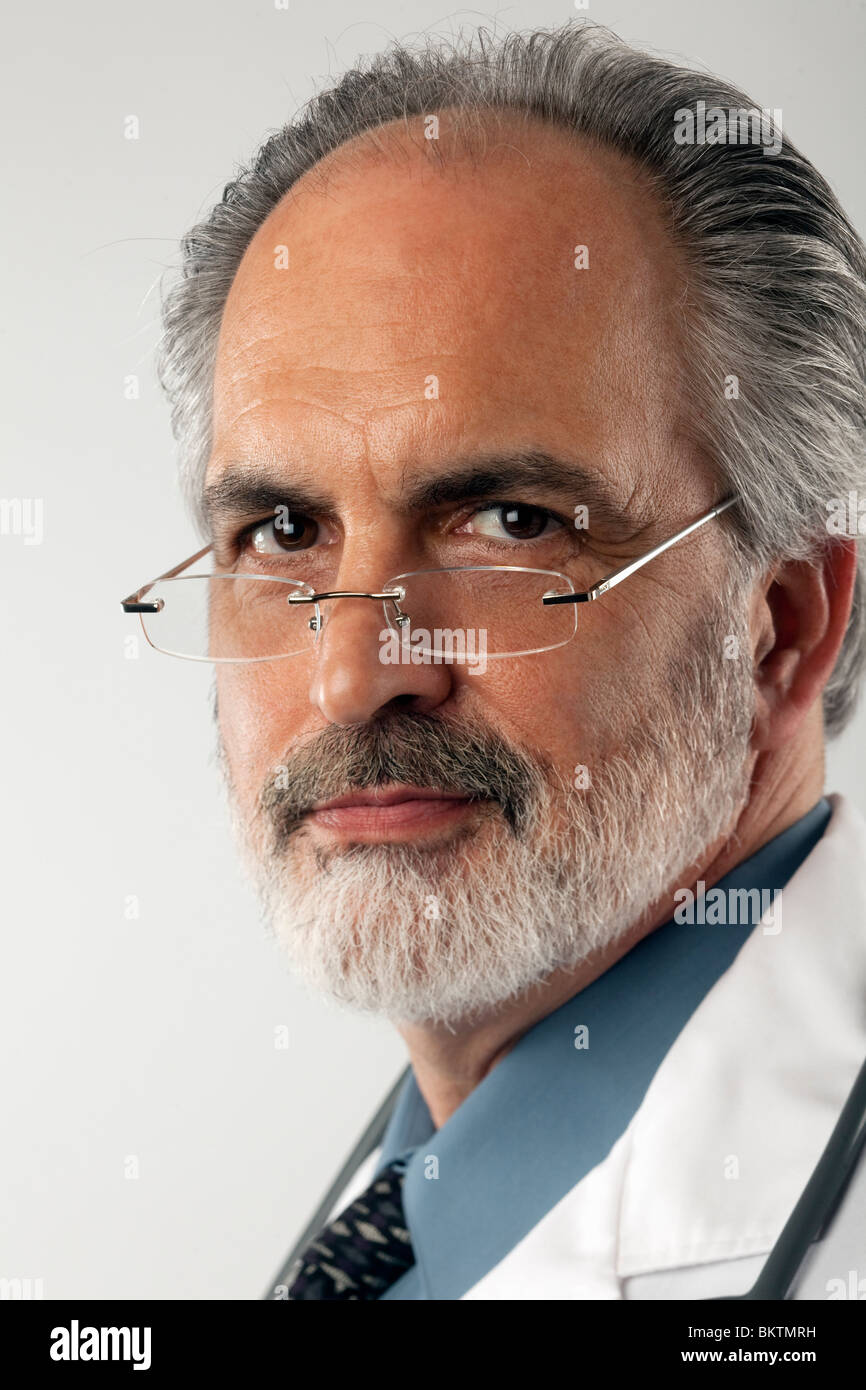 Close-up portrait of a doctor wearing glasses and a white lab coat. He is looking at the camera with a serious expression. - Stock Image