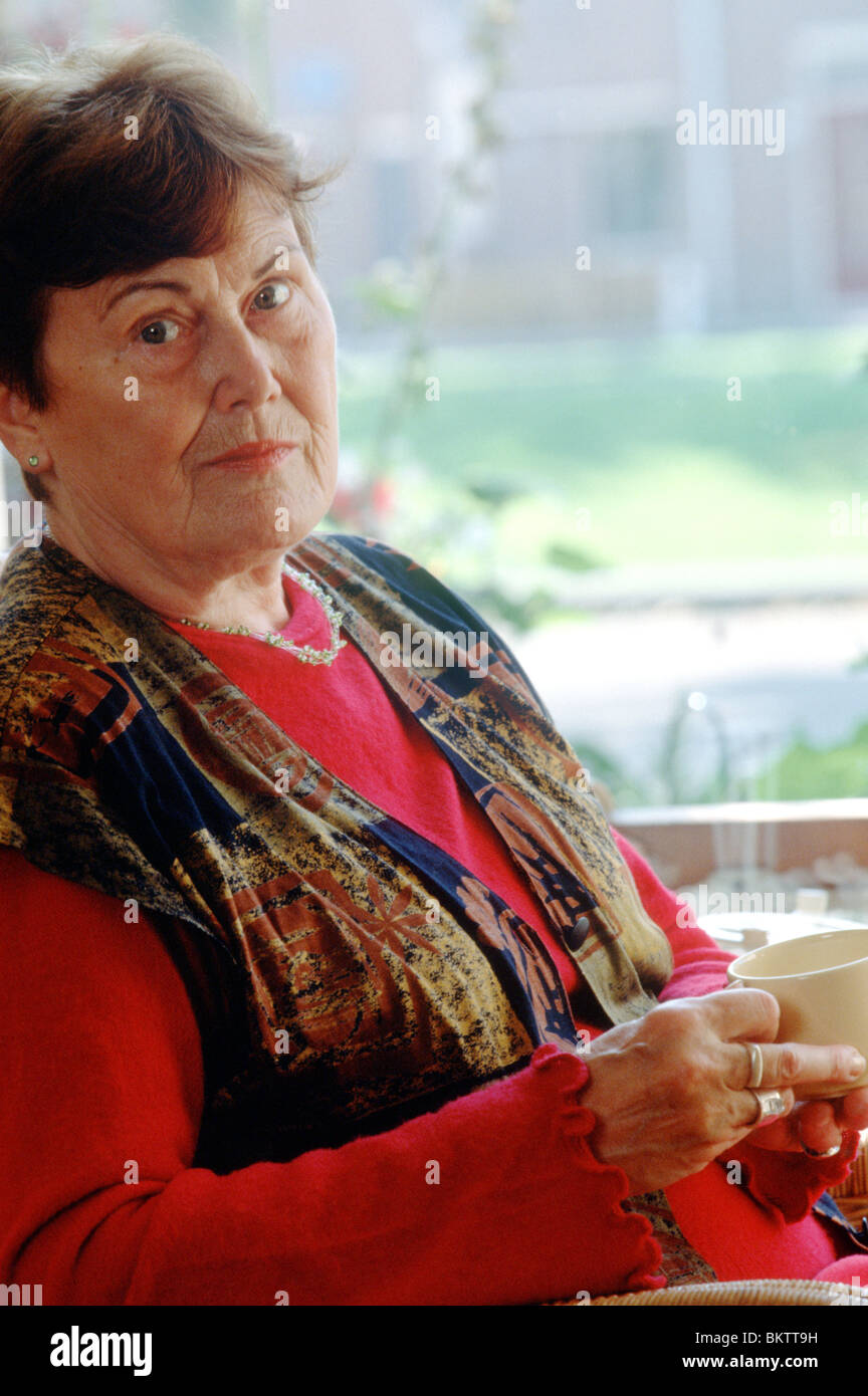 Old age woman serious look at camera drinking coffee and seated in front of window - Stock Image