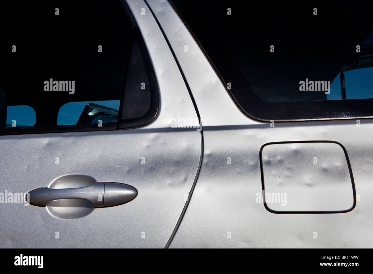 Hail damage on a car door from the Perth storm of 22/03/2010 - Stock Image