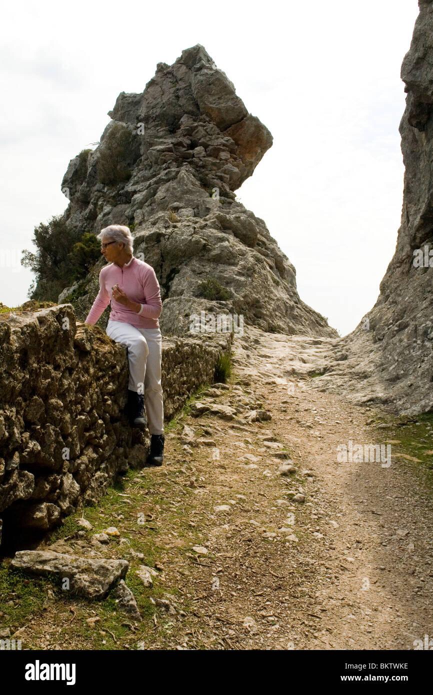 A Lady hiker's break on the pilgrimage route of Lluc (Majorca). La pause d'une randonneuse sur le chemin - Stock Image