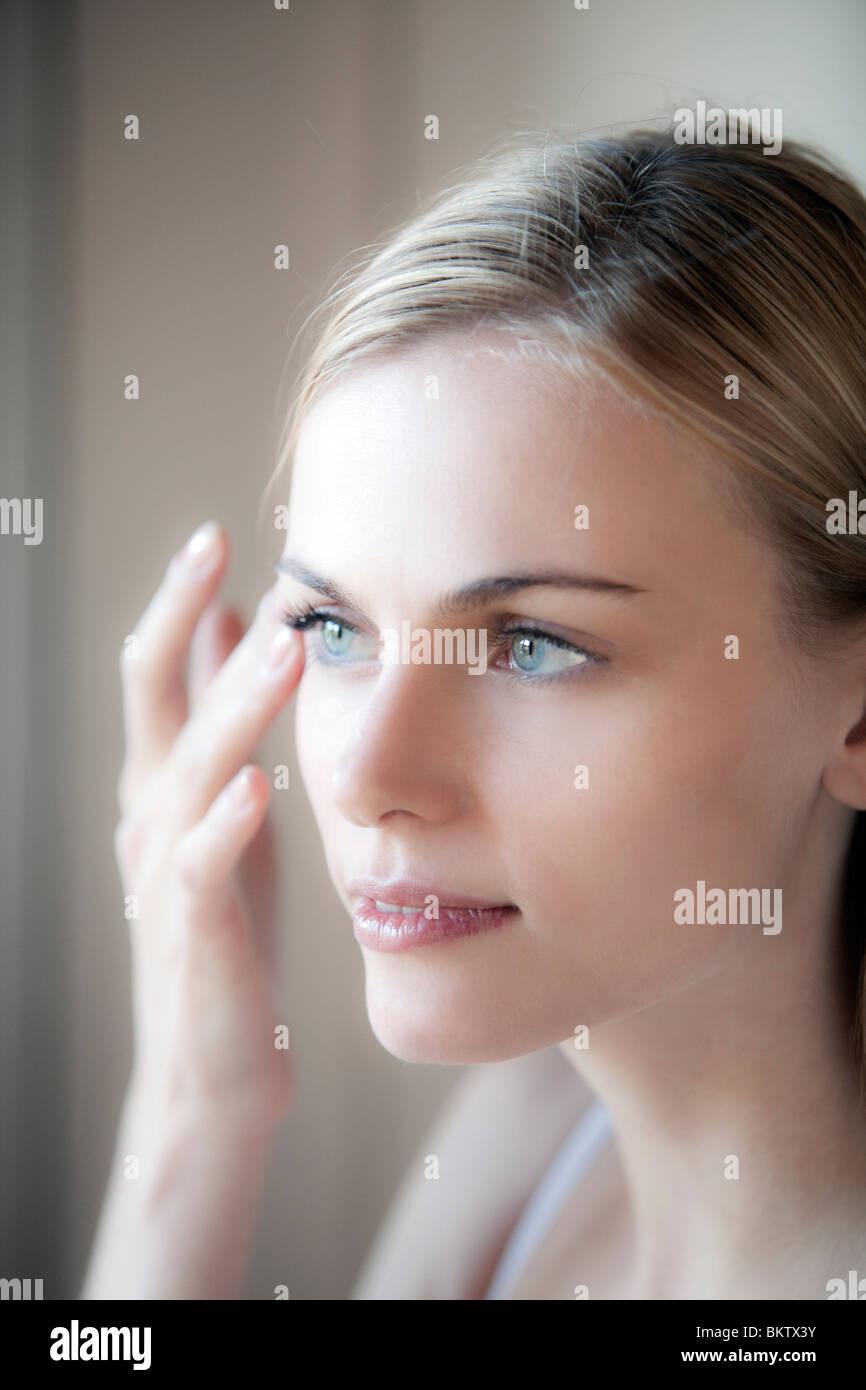 woman applies face cream - Stock Image
