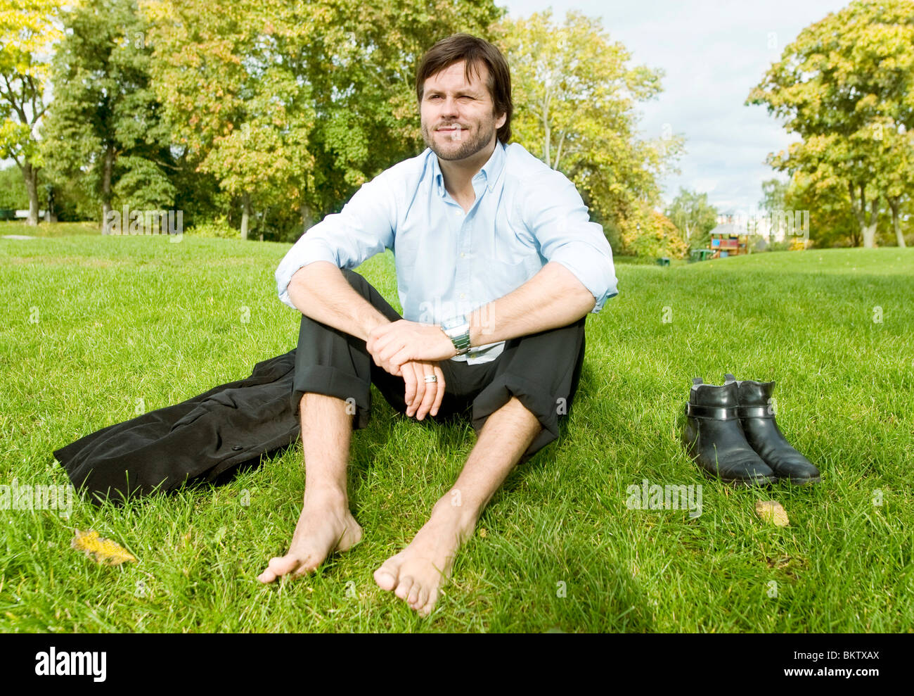 Man sitting bare foot on lawn - Stock Image