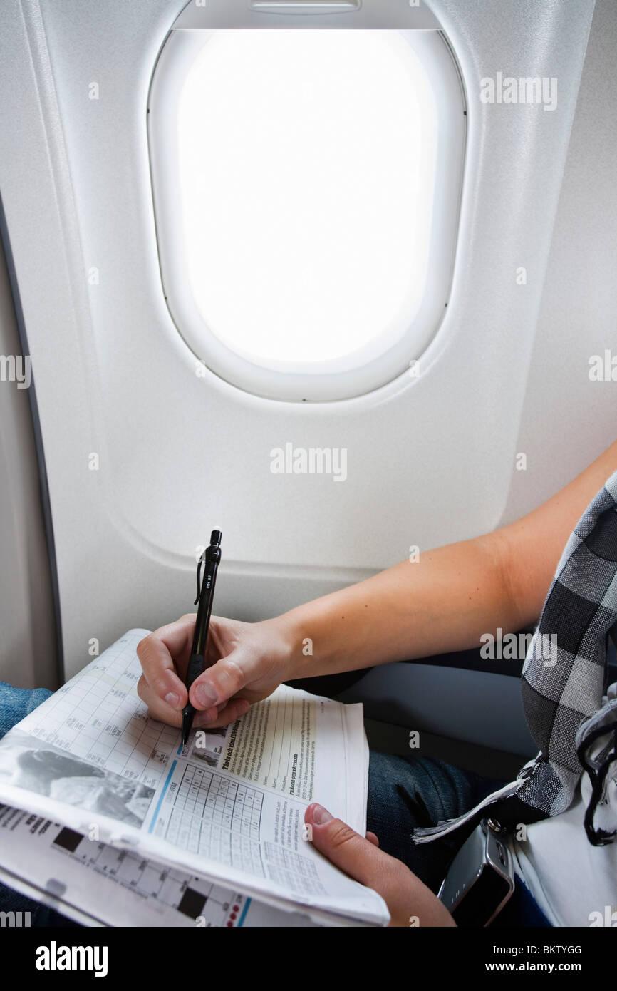 Solve crossword on airplane - Stock Image