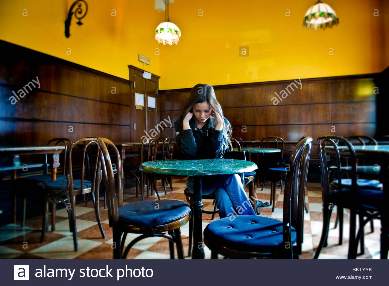 woman alone at a table in a bar - Stock Image