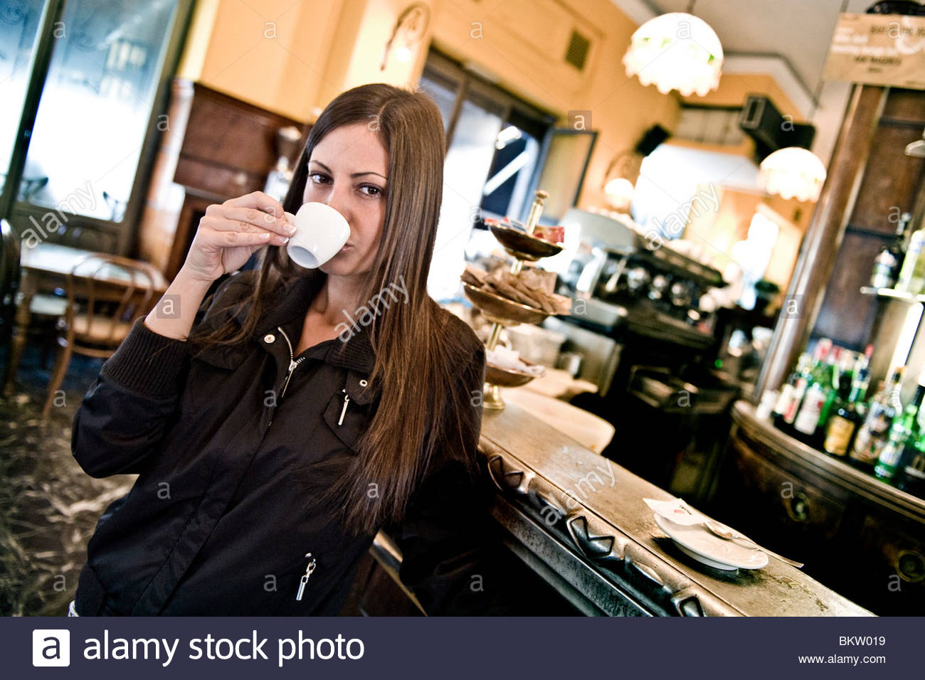 woman drinking a coffee at the bar - Stock Image