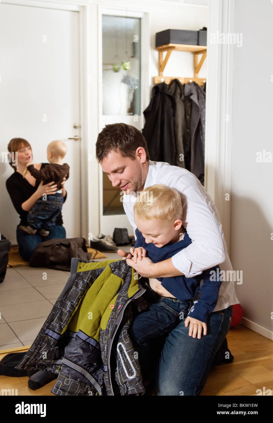 Family putting on the out door cloths - Stock Image