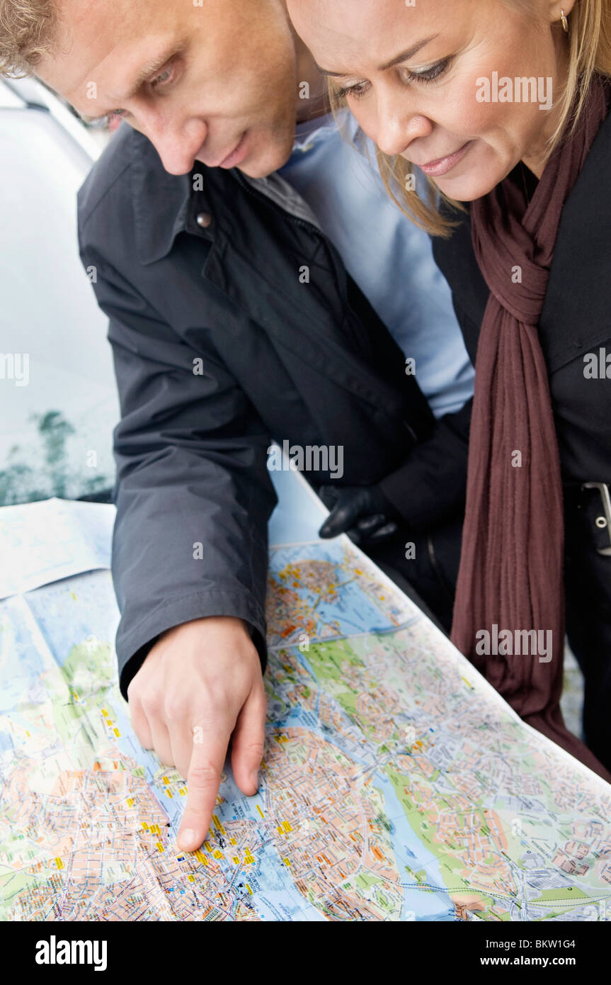 Man and woman looking at map - Stock Image