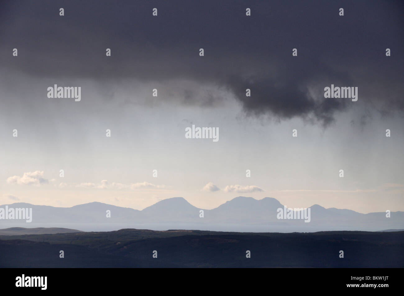 Dark clouds over Mull of Kintyre and Paps of Jura from Arran, Scotland - Stock Image
